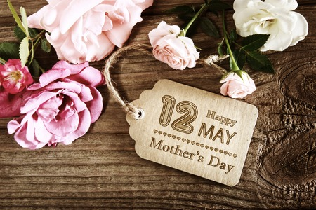 Mensaje del día de las madres con pequeñas rosas rosadas en la mesa de madera Foto de archivo