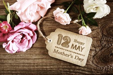 Muttertagsbotschaft mit kleinen rosa Rosen auf Holztisch Standard-Bild