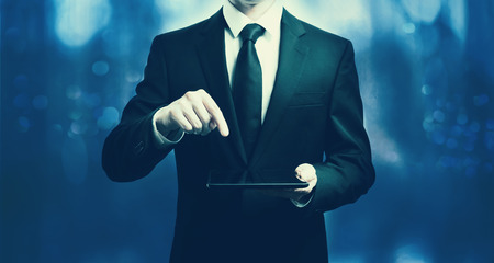 Businessman holding a tablet computer on a dark blue background Фото со стока