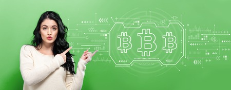 Bitcoin with young woman pointing on a green background