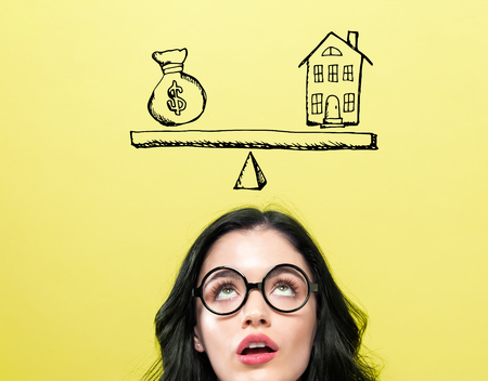 House and money on the scale with young woman wearing eye glasses Фото со стока