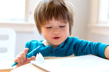 Happy toddler boy drawing at his desk
