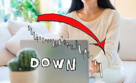 Market down trend chart with woman using her laptop in her home office