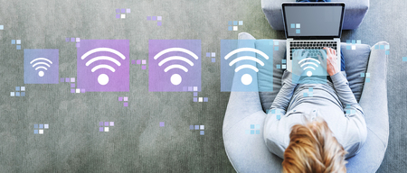 Wifi concept with man using a laptop in a modern gray chair