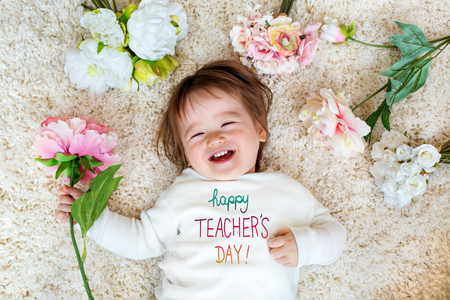 Teachers Day message with happy toddler boy with spring flowers Stock Photo - 121252934