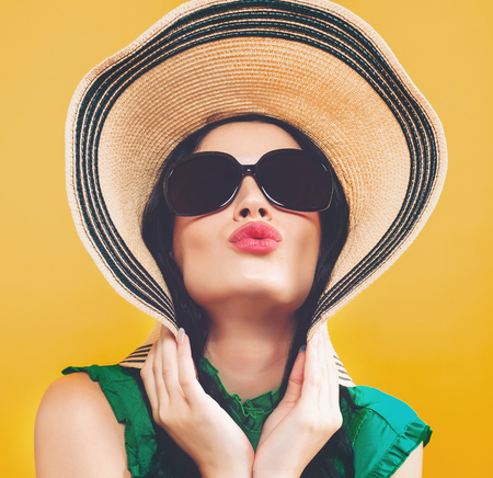 Young woman with a hat and sunglasses on a yellow background