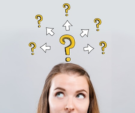 Big and small question marks with arrows with young woman looking upwards