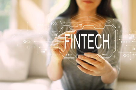 Fintech concept with woman using her smartphone in a living room 스톡 콘텐츠