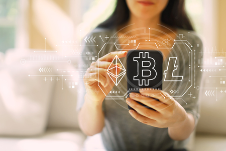 Cryptocurrency - Bitcoin, Ethereum, Litecoin with woman using her smartphone in a living room