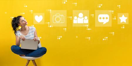 Redes sociales con mujer joven usando una computadora portátil Foto de archivo