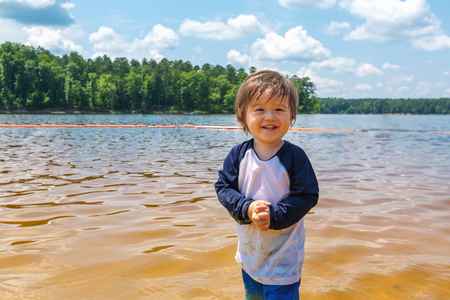Toddler boy playing in a big lake on a summer day 写真素材