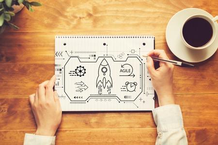 Agiles Konzept mit einer Person, die in ein Notizbuch auf einem Holztisch schreibt