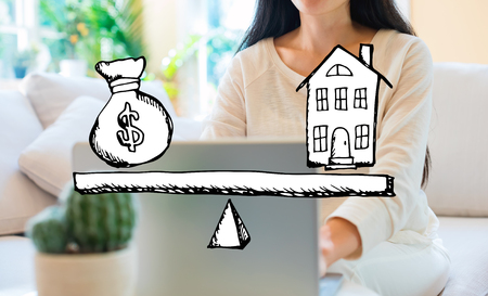 House and money on the scale with woman using her laptop in her home office