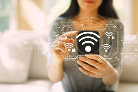 Wifi mit einer Frau, die ihr Smartphone in einem Wohnzimmer benutzt