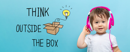 Think outside the box with toddler boy with headphones on a blue background 스톡 콘텐츠 - 122208615