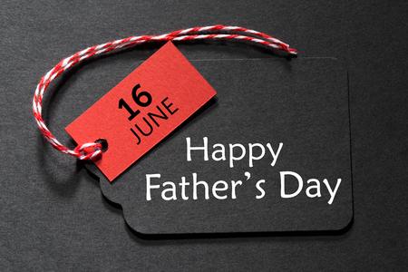 Texto feliz día del padre en una etiqueta negra con hilo rojo y blanco