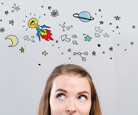 Idea rocket with young woman looking upwards