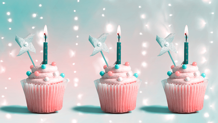 Celebratory cupcakes with decorative lit candles on a shiny background