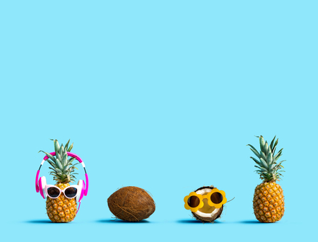 Pineapple and coconut wearing sunglasses on a solid color background Imagens