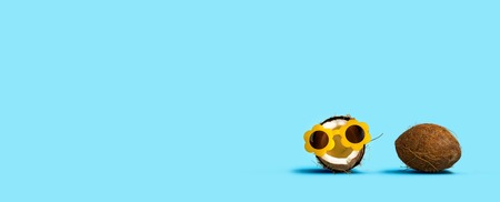 Coconut wearing sunglasses and coconut shell on a solid background