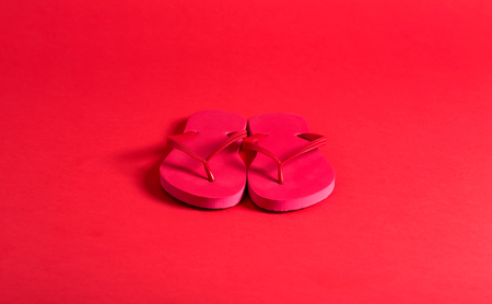 Pair of flip flop sandals on a red background