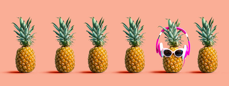 One out unique pineapple wearing headphones on a solid color background