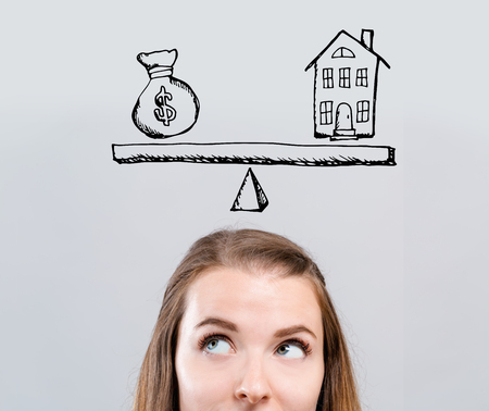 House and money on the scale with young woman looking upwards