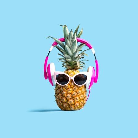 Piña con auriculares sobre un fondo de color sólido