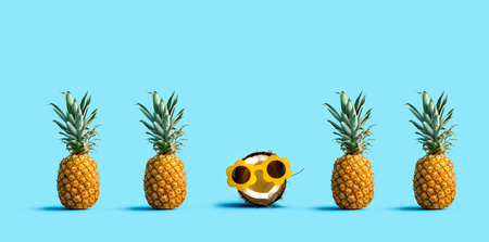 One out unique coconut wearing sunglasses with many pineapples