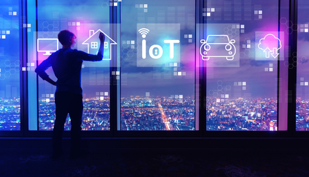 IoT theme with man writing on large windows high above a sprawling city at night
