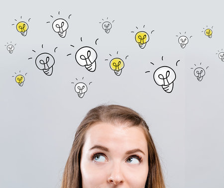 Many light bulbs with young woman looking upwards