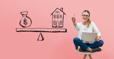 House and money on the scale with young woman using her laptop