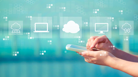 Cloud computing with person holding a white smartphone Banco de Imagens