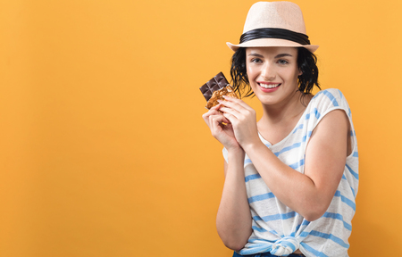 Young woman holding chocolate on a solid background