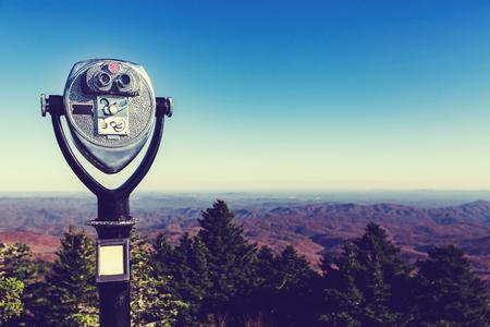 Verrekijker die op munten werkt en uitkijkt over de Blue Ridge Mountains, NC