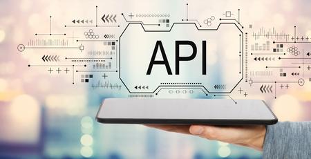 API-Konzept mit Mann, der einen Tablet-Computer hält Standard-Bild