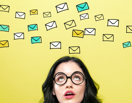 Many emails with young woman wearing eye glasses