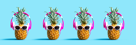 Pineapples wearing headphones on a solid color background
