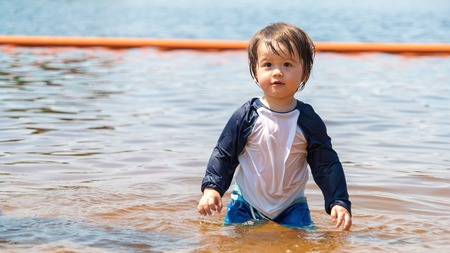 Toddler boy swimming in a big lake on a summer day