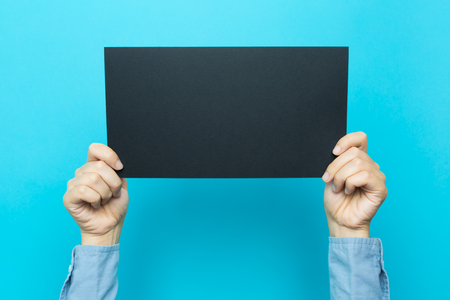 Hand holding up a note card on a blue background Stock Photo