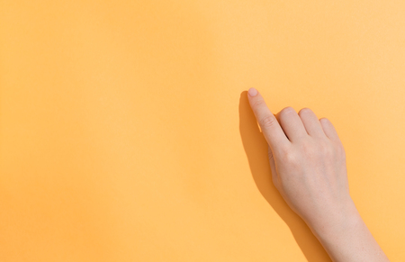 Person pointing to something on a orange background 写真素材 - 123497532