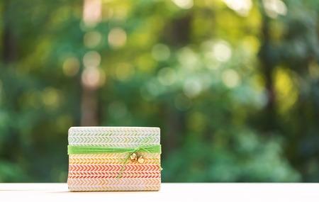 在闪亮的绿色森林背景的礼物盒