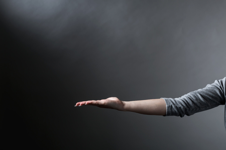 Person holding something on a gray background