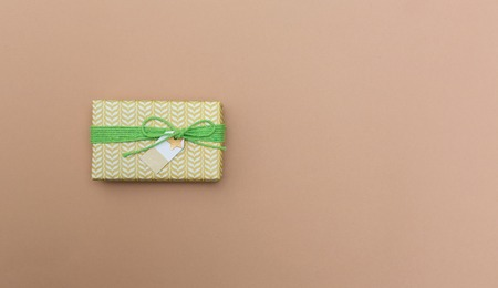 A gift box on a light brown paper background Stock Photo