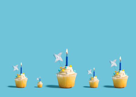 Big and small celebratory cupcakes with decorative lit candles