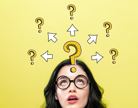 Big and small question marks with arrows with young woman wearing eye glasses