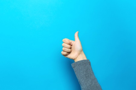 Person doing thumbs up gesture on a blue background Stock fotó