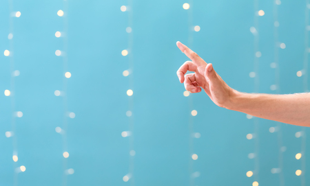 Person pointing on a shiny light blue background