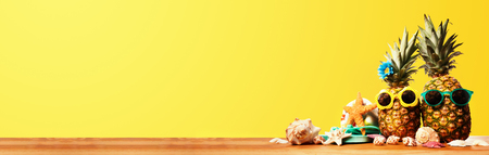 Pineapple wearing sunglasses on a yellow background Stock Photo