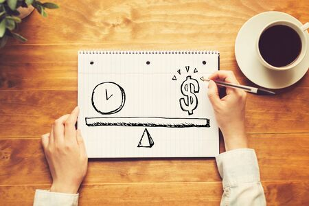 Time and money on the scale with a person holding a pen on a wooden desk